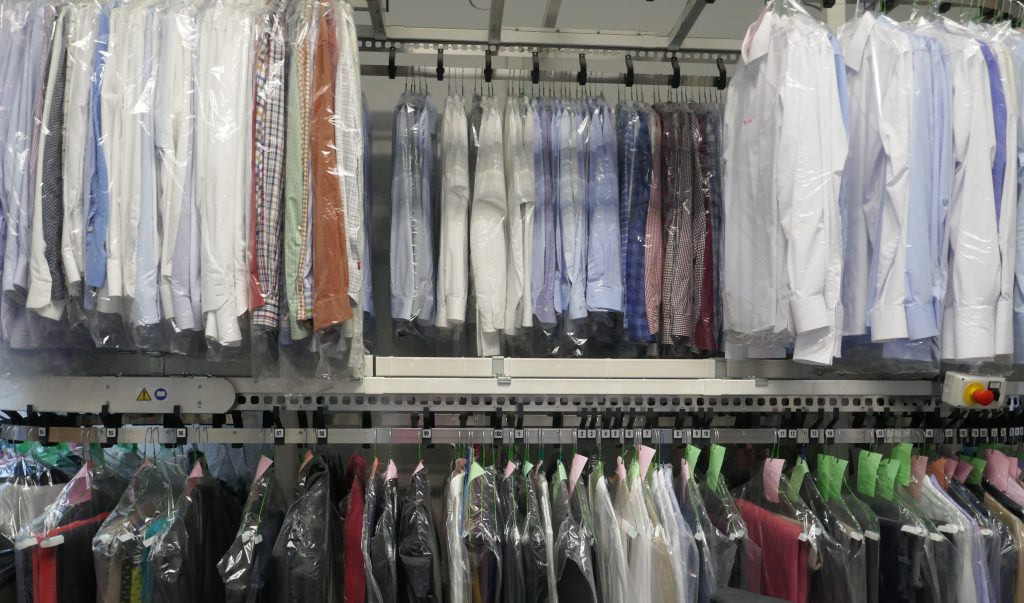 Freshly cleaned shirts and blouses in a textile cleanig, hangind on hangers and packed in plastic wrap.