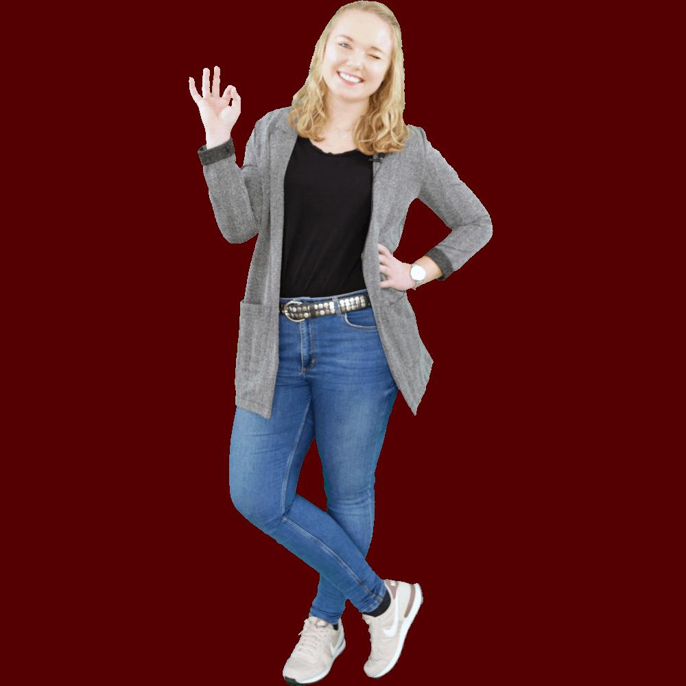 Junge blonde Frau posiert lächelnd vor der Kamera und macht ein OK Zeichen