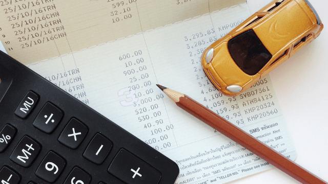 ein Taschenrechner, Bilanzen und ein Bleistift liegen auf dem Tisch
