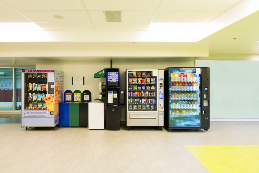 Various vending machines and trash cans lined up against a wall.